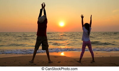 Boy And Girl Making Exercises On The Beach At Sunset