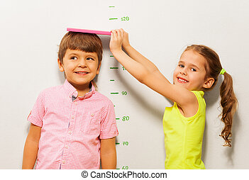 Boy and girl measure height by wall scale at home