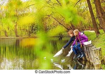 Boy and girl near the pond play with paper boats
