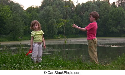 boy and girl near young plant against pond