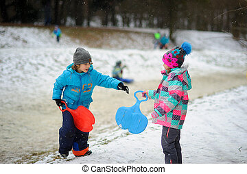 Boy and girl of younger school age in the winter park about...