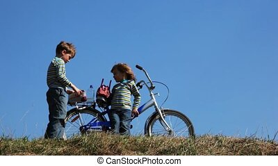 boy and girl on field stay near bicycle and take from bags toys on field