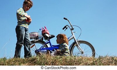 boy and girl on field stay near bicycle play with toys and take photo form bag. time lapse