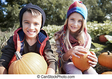 Boy and girl on pumpkin field
