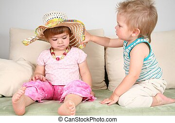 boy and girl on sofa in straw hat with beads