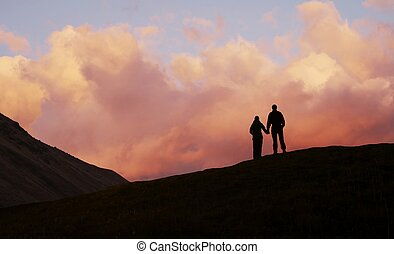 Boy and girl on sunset background