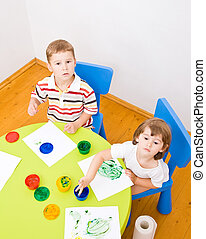 Boy and girl paint colors sitting at the table