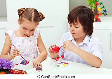 Boy and girl painting easter eggs