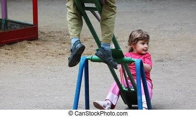 boy and girl play at seesaw together on playground