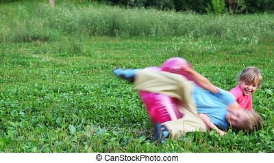 boy and girl play with children's inflatable armchair on field in park