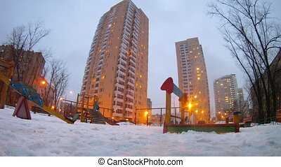 Boy and girl play with snow in playground town in evening