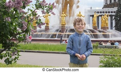 boy and girl playing and throwing flower petals in front of soviet fountain