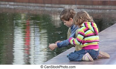 boy and girl playing fishing at the city pond