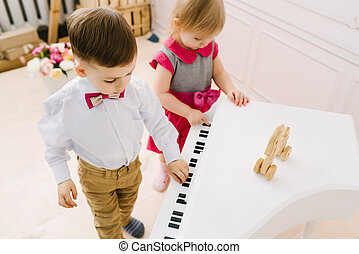 boy and girl playing on the piano