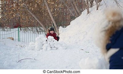 boy and girl playing outdoors in winter. Children throw snowballs
