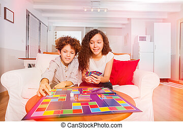 Boy and girl playing tabletop game at home