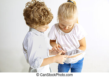 Boy and girl playing together on white studio background