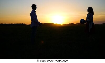 boy and girl playing with ball at sunset