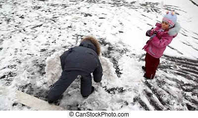 boy and girl playing with snow and building a fortress