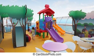 boy and girl plays on playground on deck of cruise ship in Persian Gulf.