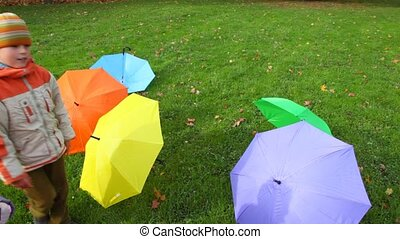 boy and girl puts umbrellas in a row in park