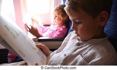 boy and girl read behavior rules safety instruction in plane