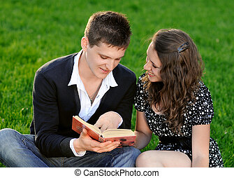 Boy and girl reading a book sitting on the grass