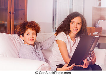 Boy and girl reading book while doing homework