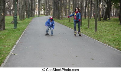 Boy and girl ride in autumn park on rollerblades and...