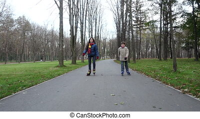 Boy and girl ride in autumn park on rollerblades - Smiling...