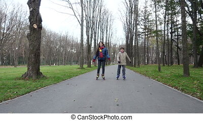 Boy and girl ride in autumn park on rollers