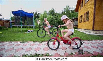 Boy and girl ride on bike, other boy run, father makes kebab