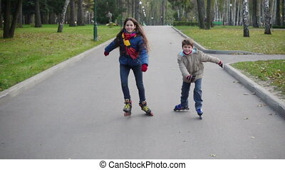 Boy and girl ride together in autumn park on rollers