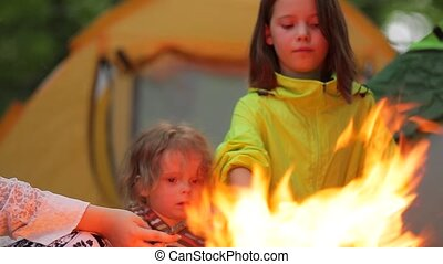 Boy and girl roast marshmallows over a campfire. - Late...