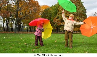 boy and girl rotates with umbrellas in autumn park