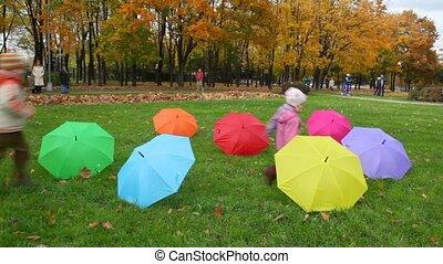 boy and girl runs about umbrellas in autumn park