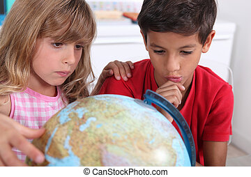Boy and girl sat with globe