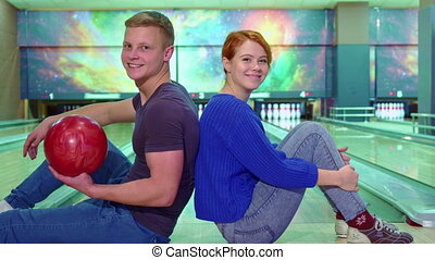 Boy and girl show their thumbs up at the bowling -...