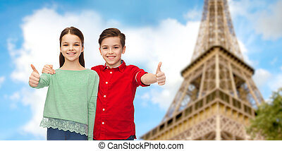 boy and girl showing thumbs up over eiffel tower