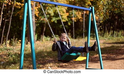 Boy and girl singing on swings