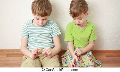 boy and girl sit on floor leaning against wall