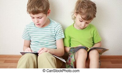 boy and girl sit on floor leaning against wall and read books