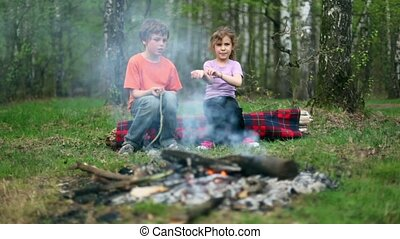 Boy and girl sit on log and watch at bonfire burn
