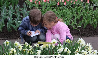 Boy and girl sit to path between flowers - boy and girl sit...