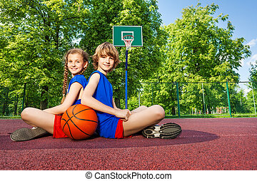 Boy and girl sit with backs close on playground - Boy and...