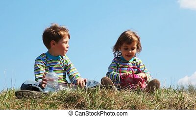 boy and girl sits on field and talk