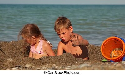 Boy and girl sitting in small pit in sand and digging - Boy...