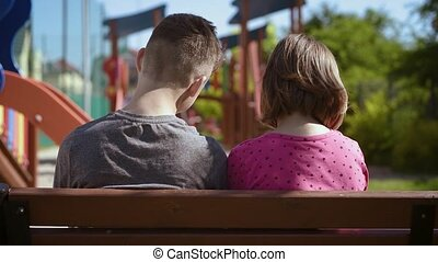 Boy and girl sitting on the bench