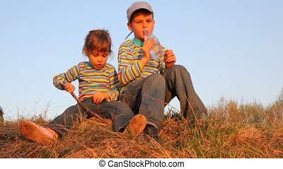 Boy and girl sitting on the grass. He drinking water, she...