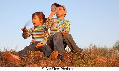 Boy and girl sitting on the grass. He drinking water, she talking about something